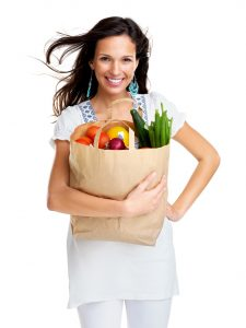 Happy young woman carrying a shopping bag full of groceries
